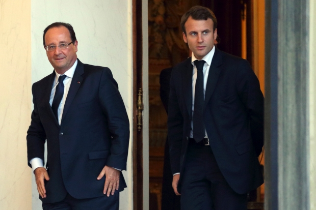 French President Hollande and economy advisor Macron walk in the Elysee Palace in Paris